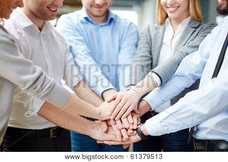 Arms of business partners keeping their hands on top of each other symbolizing teamwork