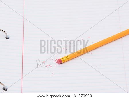 Closeup of a pencil on a notebook page with the word homework partially erased. Back to school concept.