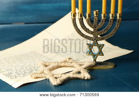 Menorah, star of David and page of Genesis book on wooden background