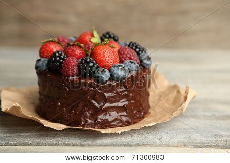 Tasty chocolate cake with different berries on wooden table