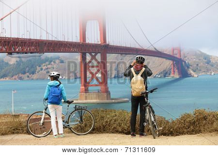 Golden gate bridge - biking couple sightseeing in San Francisco, USA. Young couple tourists on bike tour enjoying the view at the famous travel landmark in California, USA.
