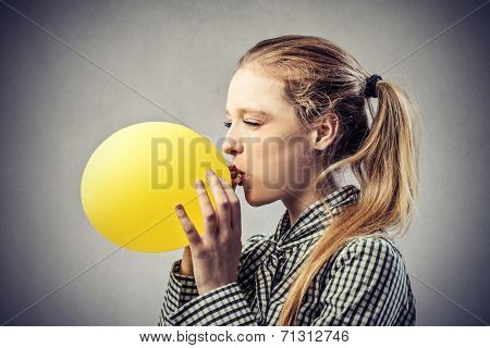 beautiful woman is blowing up a yellow balloon
