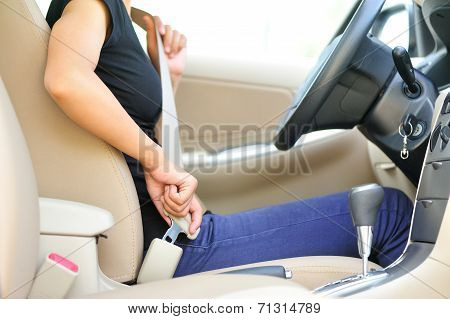 woman driver buckle up the seat belt before driving car