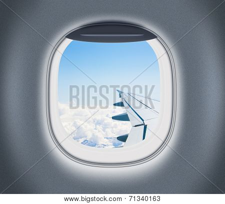 Airplane or aeroplane window with wing and cloudy sky behind. Air travel and flight concept.