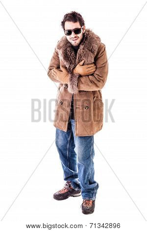 a cheerful young man wearing an expensive sheepskin furry coat isolated over a white background and shivering for the cold poster