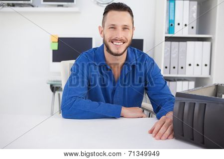 Computer engineer sitting at desk smiling at camera in his office