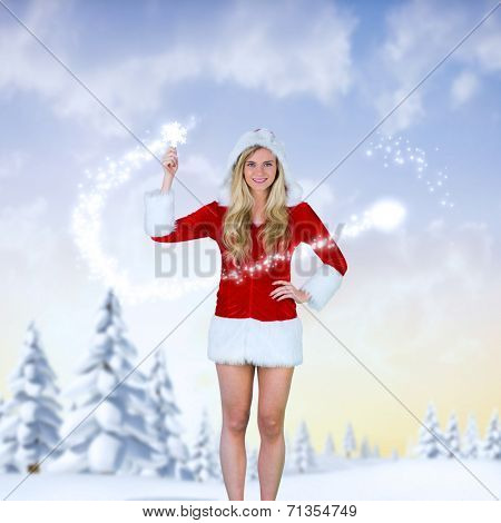 Pretty girl in santa outfit holding hand up against snowy landscape with fir trees poster