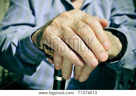 closeup of the hands of an old man with a walking stick