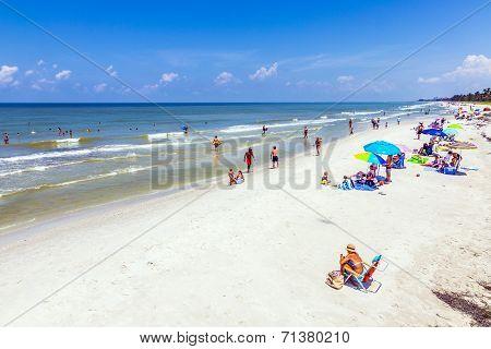 People Enjoy The Beautiful White Beach At Naples Pier