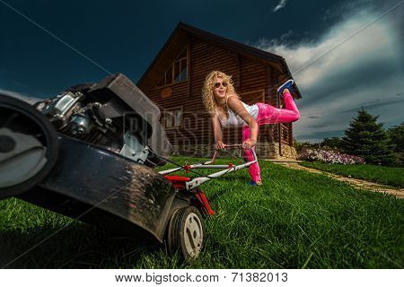 Beautiful laughing housemaid with lawn mower near country house.