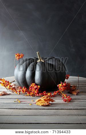 Black colored pumpkin with berries and leaves on table