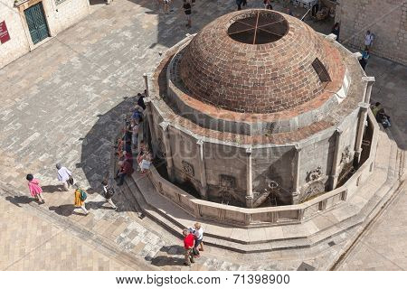 DUBROVNIK, CROATIA - MAY 26, 2014: Tourists around large Onofrio's Fountain on Stradun, main pedestrian street in town. Fountain was part of a water-supply system.