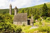 Saint Kevin Church (Kitchen) is a symbol of Ireland and part of Glendalough (Gleann Da Loch) Heritage Center in the Wicklow Mountains. The early monastic settlement was built around the years 500 and includes a famous Round Tower about 30 m high. poster