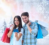 Couple with shopping bags and credit card against snowy landscape with fir trees poster