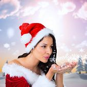 Pretty girl in santa outfit blowing against snowy landscape with fir trees poster
