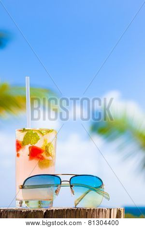 glass of chilled cocktail mohito and sunglasses on table near the beach