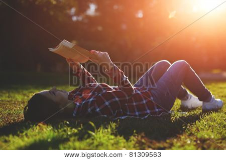 A young woman lying on the grass and reading a book lovely young girl reading a book outdoors