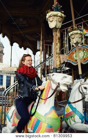 Attractive young  woman enjoying time while riding on a merry go round on holidays