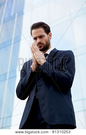 Portrait of a handsome young businessman standing with palms together having big hope