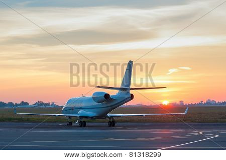 Airplane stay in airport. Business jet on the apron for aircraft. The background of the city. poster