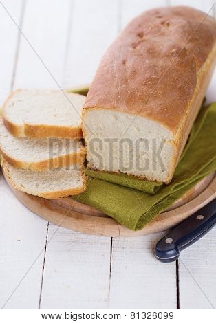Sliced loaf of homemade bread on board on white wooden background. Selective focus. poster