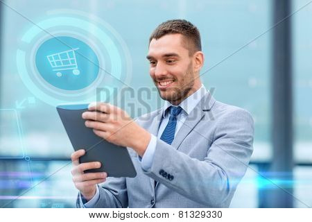 business, sale, technology and people concept - smiling businessman with tablet pc computer and virtual shopping trolley icon hologram on city street