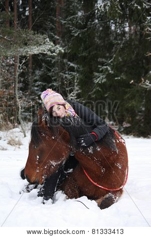 Teenager Girl And Brown Horse Lying In The Snow