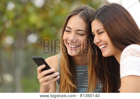 Two Happy Women Friends Sharing A Smart Phone