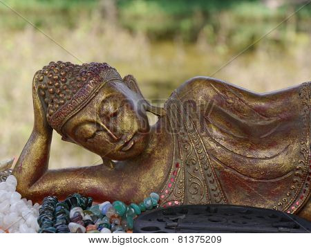 Small gold and red reclining buddha ornament
