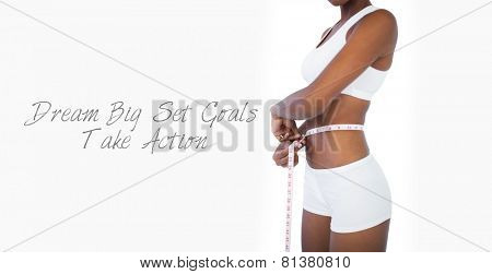 Young woman measuring her waist during diet on white background