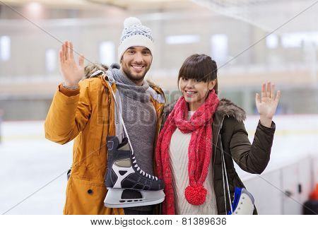 people, friendship, sport and leisure concept - happy couple with ice-skates on skating rink