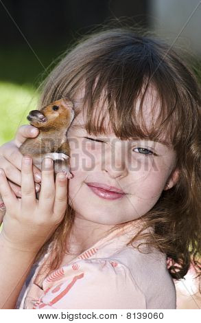 Young girl with brown pet hamster
