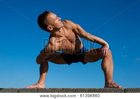 Happy Athletic Man Doing Yoga Asanas In The Park At Sunny Day