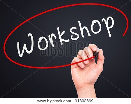 Man Hand writing Workshop with marker on transparent wipe board.