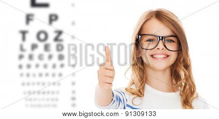 education, school, childhood, people and vision concept - smiling cute little girl with black eyeglasses showing thumbs up gesture over eye chart background poster
