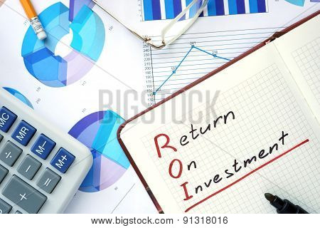 Notepad with word ROI return on investment concept and marker. poster