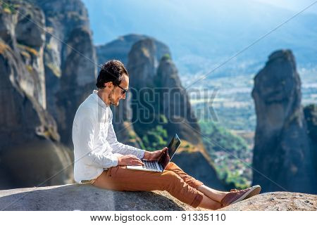 Man with laptop on the mountains