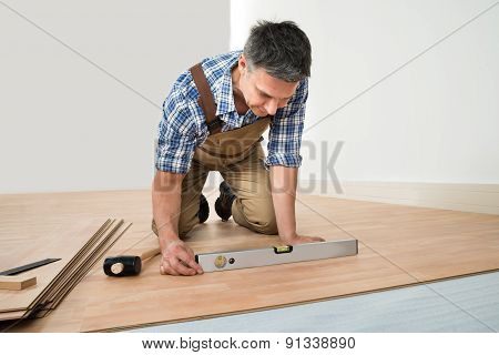 Carpenter Installing New Laminated Wooden Floor At Home poster