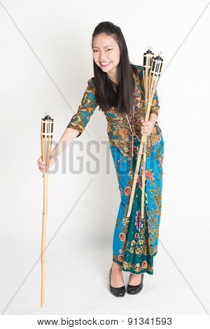 Full body portrait of Southeast Asian woman in batik dress hands holding tiki torch standing on plain background.