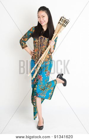 Full body portrait of Southeast Asian woman in batik dress hands holding bamboo oil lamp standing on plain background.