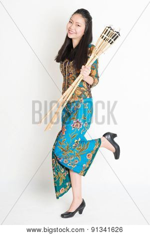 Full body portrait of Southeast Asian woman in batik dress hand holding pelita or oil lamp standing on plain background.