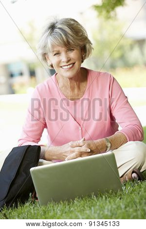 Senior woman using laptop outdoors