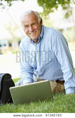 Senior man using laptop outdoors