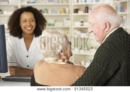 Senior couple in pharmacy with pharmacist