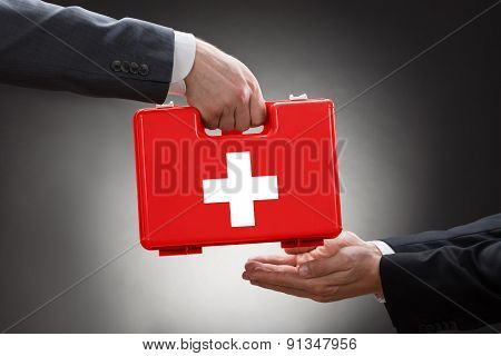 Close-up Of A Person's Hand Giving First Aid Box