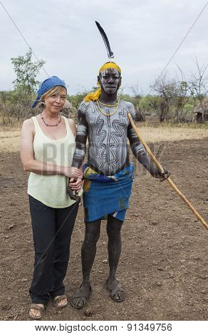 European Woman And Man From Mursi Tribe In Mirobey Village. Mago National Park. Omo Valley. Ethiopia
