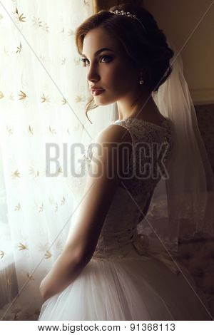 fashion photo of beautiful sensual bride with dark hair in luxurious lace wedding dress posing at home poster