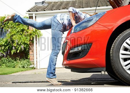 Woman Looking At Car Engine With Head Disappearing Under Hood