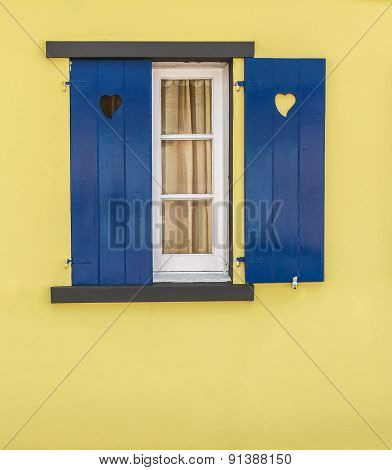 Detail Of Blue Window With Hearts And Yellow Wall