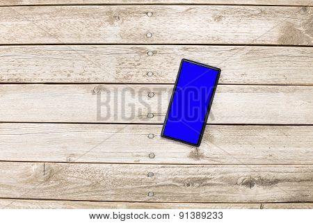 Mobile Phone On Wooden Floor